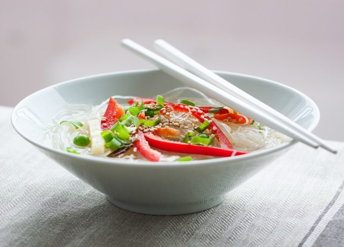 Asian rice noodles with vegetables and sesame in a bowl on a linen textile background, closeup