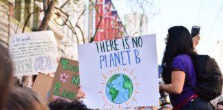 jovem levanta cartaz para conscientizar sobre os impactos do aquecimento global - mudanças climáticas